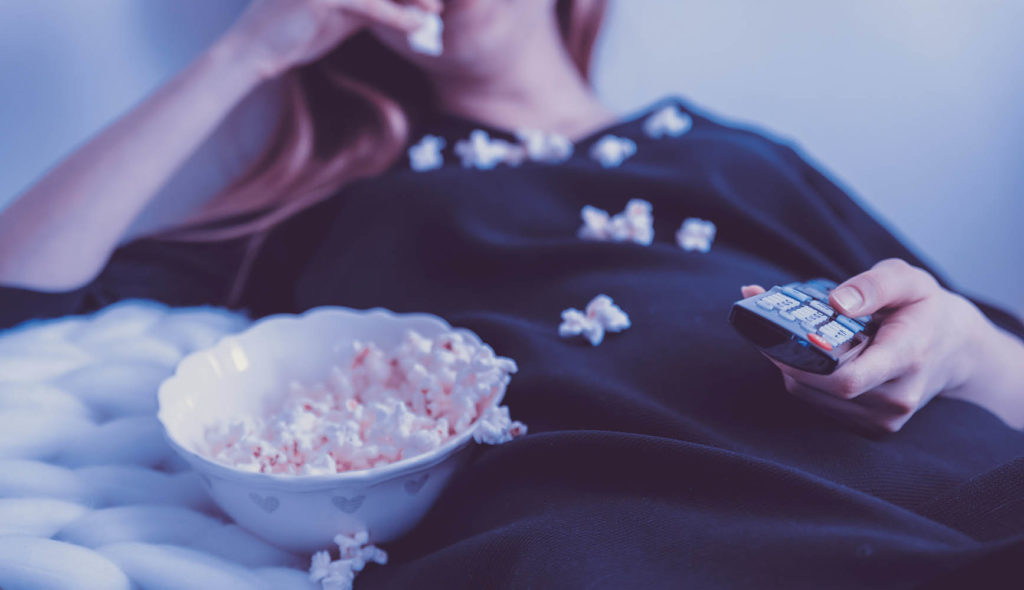 ベッドの上でポップコーン食べながらテレビで映画鑑賞する女性の写真
