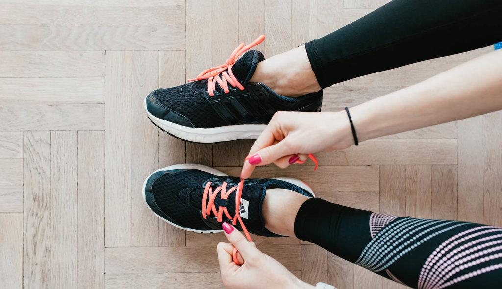 ランニングシューズの蛍光オレンジの靴紐を結ぶピンクのネイルの手の写真