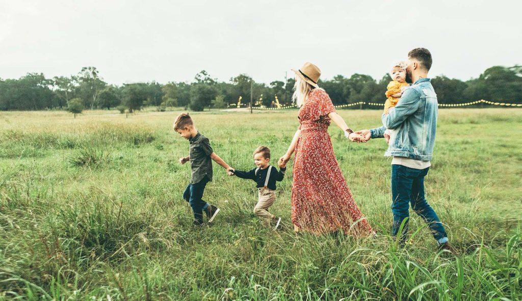 手を繋いで野原を歩く5人家族