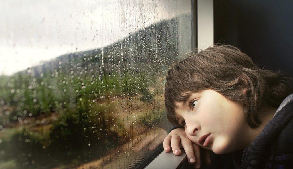 雨の窓の外をぼーっと見つめる少年の写真