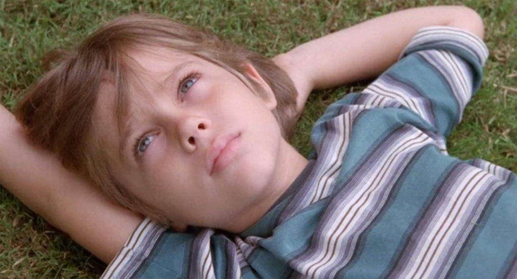 芝生に寝転がって空を見つめる少年「ボク」