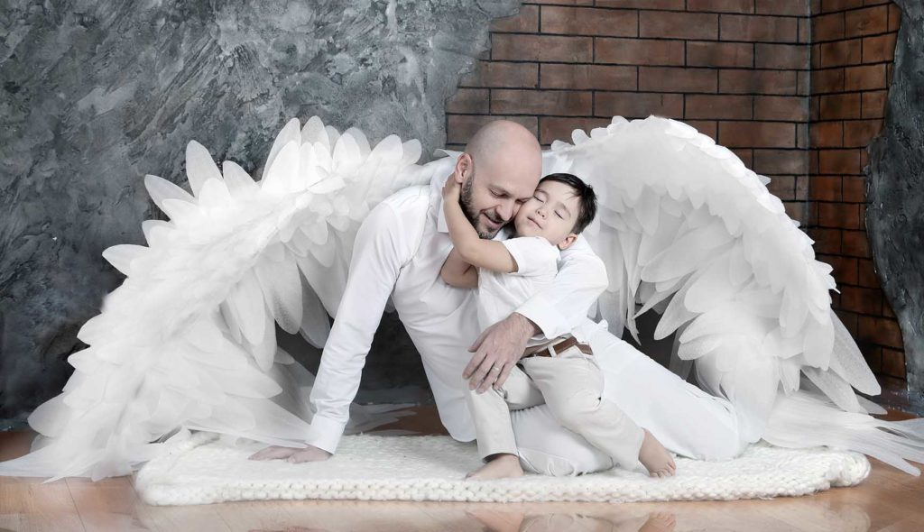天使の羽の生えたパパに抱きつく少年