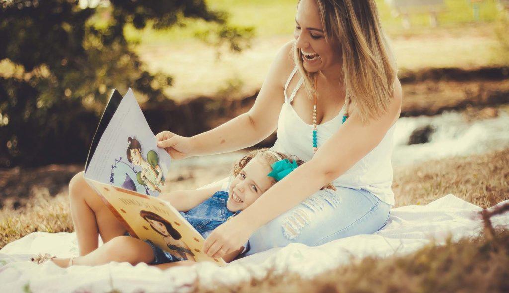 ピクニックで母の膝枕で絵本読んでもらう少女