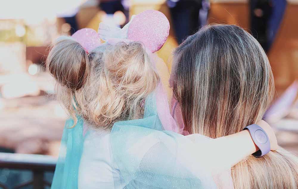 ディズニーのコスプレしている女の子を抱っこしている女性の後ろ姿写真