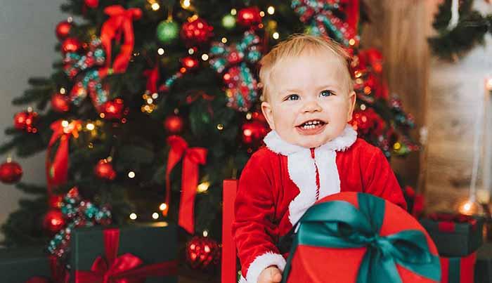 サンタの服着た子供とクリスマスツリーとプレゼント