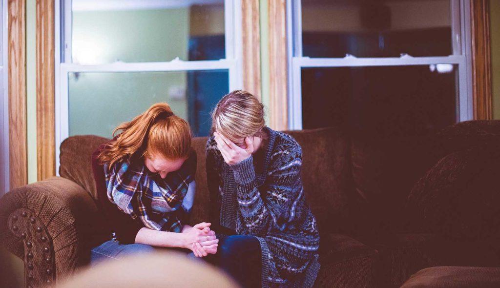 手を取り涙する母と娘の写真