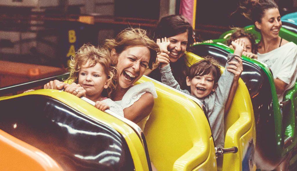 遊園地の乗り物に乗ってはしゃぐ親子たち