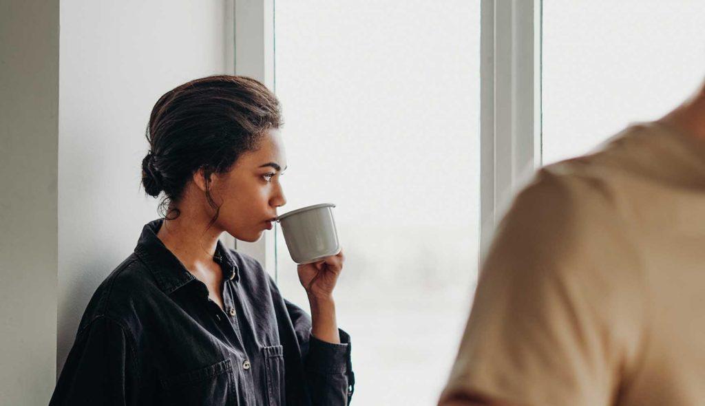 彼氏と離れた位置で、コーヒーを口にしながら物憂げに窓の外を見つめるパジャマ姿の彼女