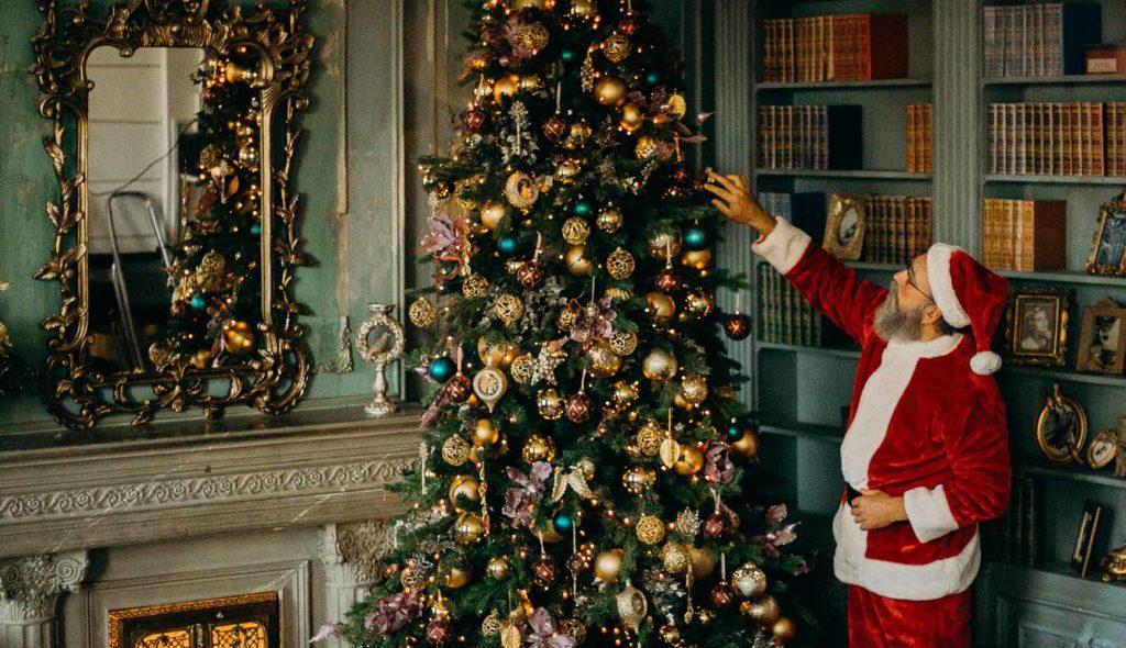 サンタクロースがツリーを飾りつけ