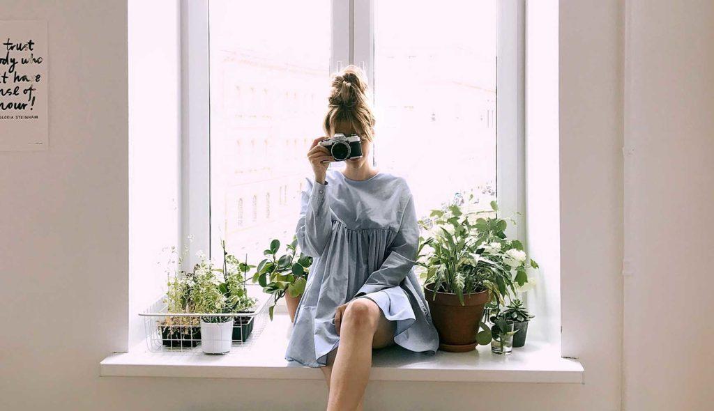 若い女の子が窓際に座ってカメラをのぞいている