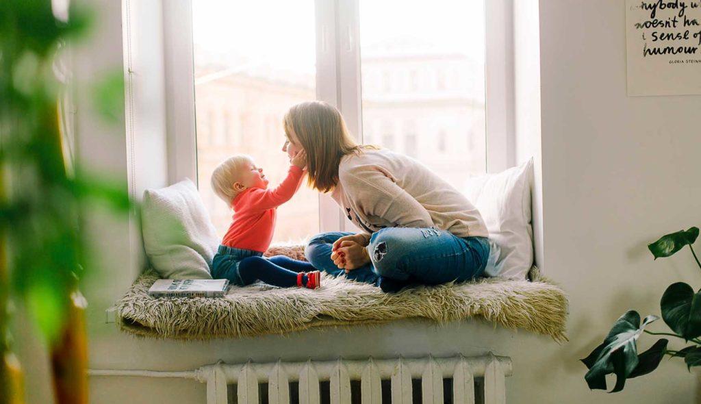 子供に顔を近づける女性と、その顔に触れる2歳くらいの子供