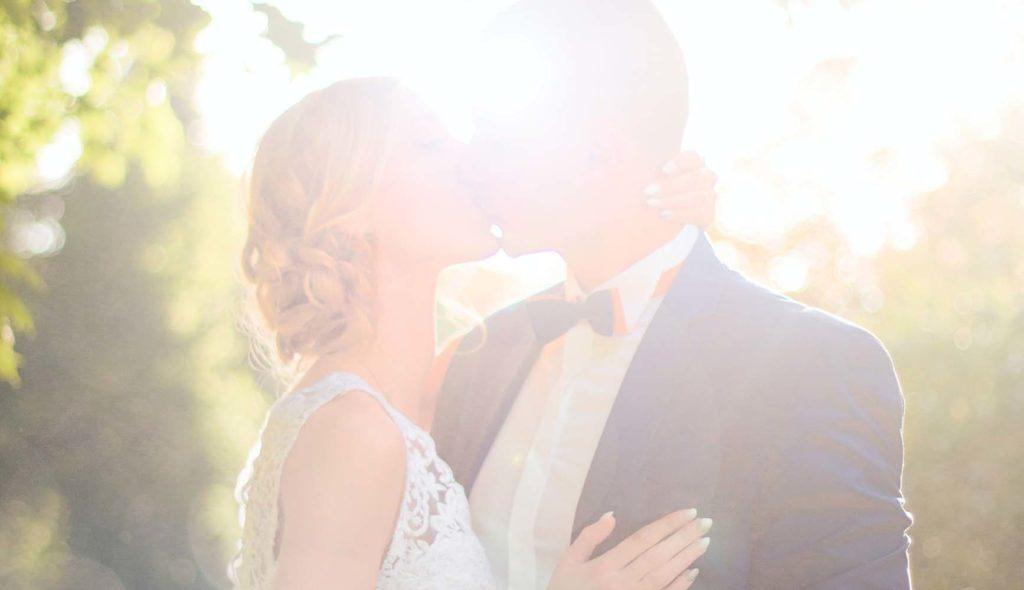 逆光で白く輝く背景の中、キスする新郎新婦