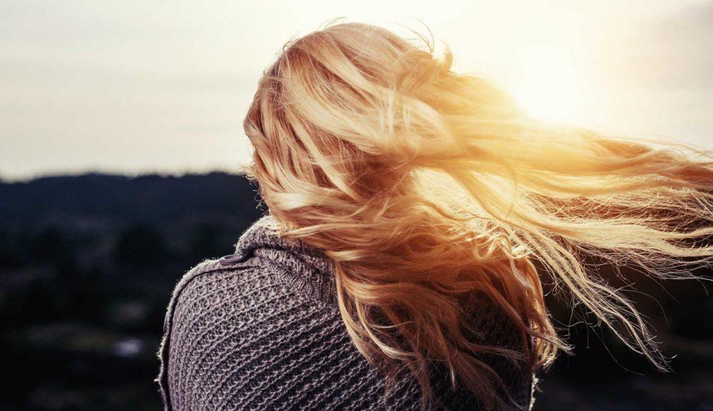 夕暮れ時、髪をなびかせ、ひとり空を見つめる女性の背中