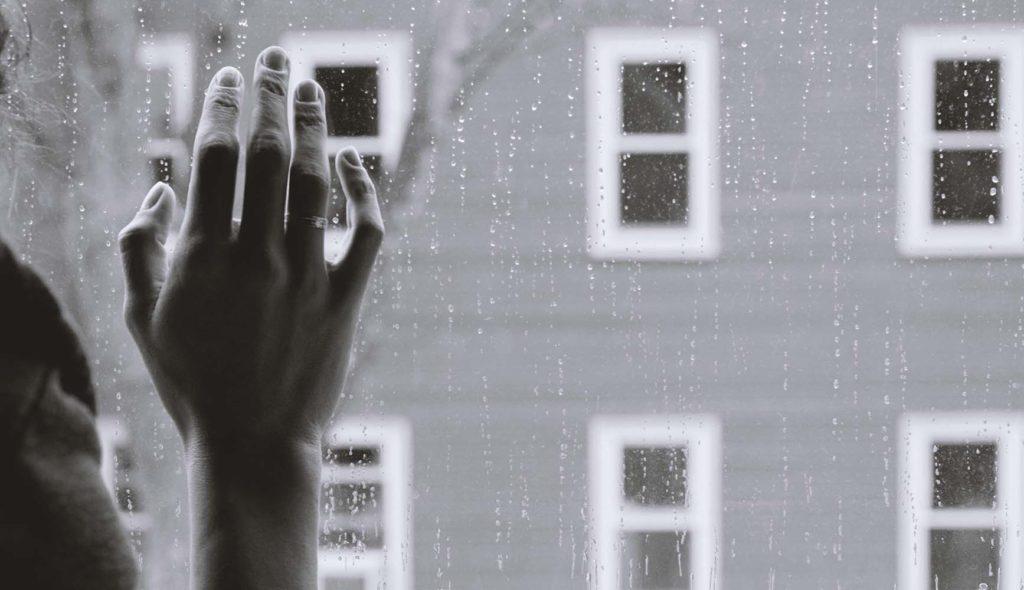 雨粒の窓から外を眺める女性の手のモノクロ写真