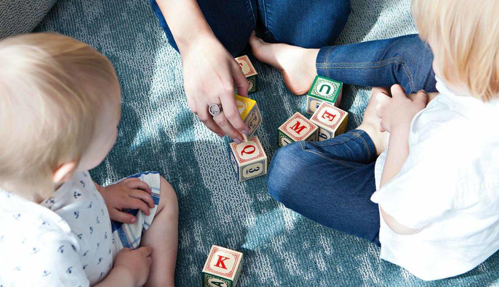 アルファベットの書かれた積み木で遊ぶ女性と2人の子供