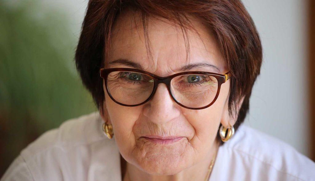 メガネをかけこちらを見つめる初老女性