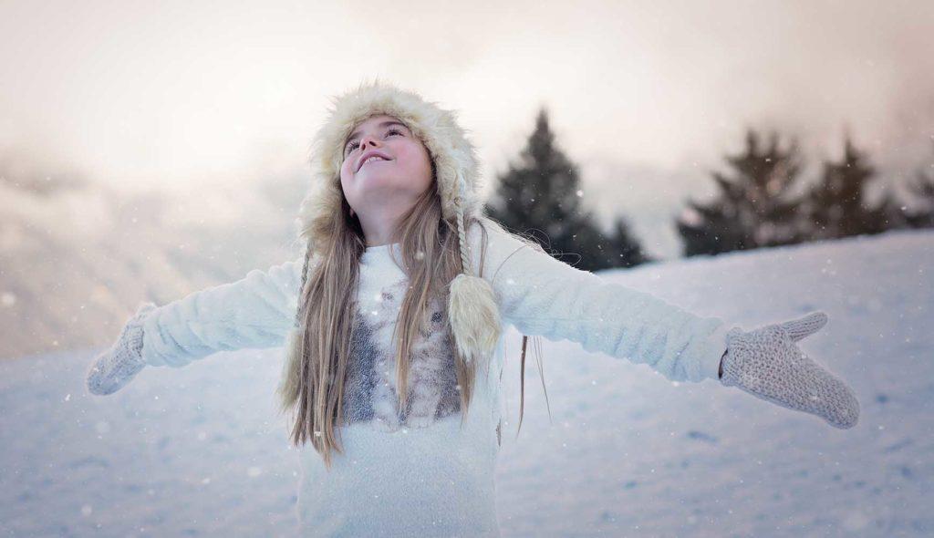 手袋をした両手を広げ、空に向かって笑顔を放つ少女