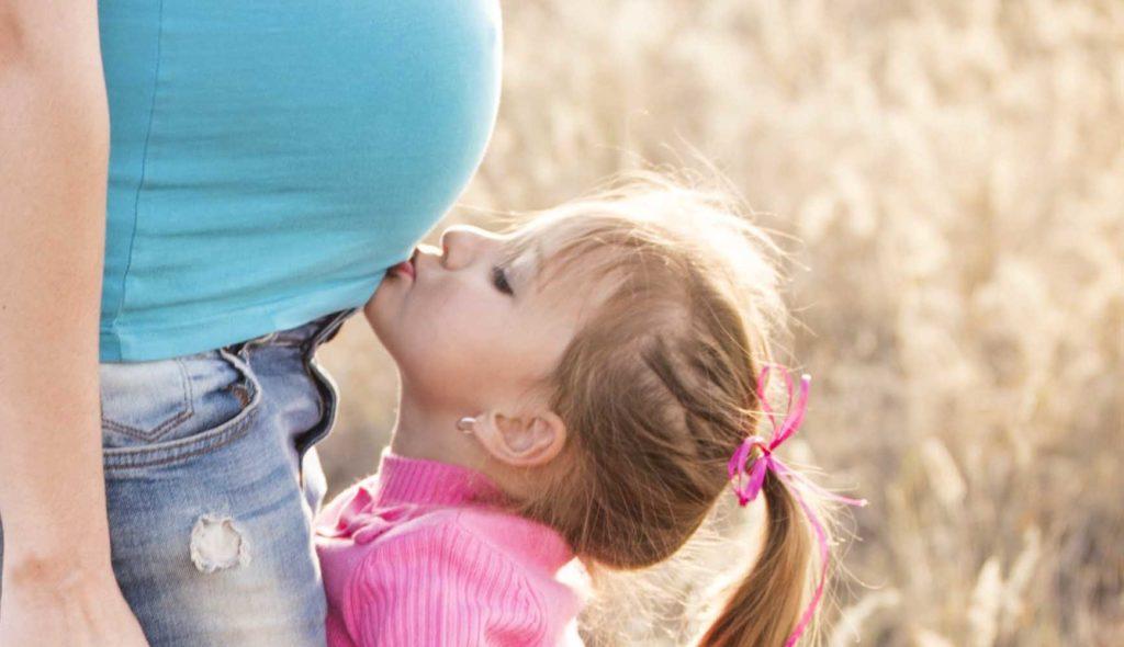 妊婦の母のお腹にキスをする3歳くらいの女の子の写真