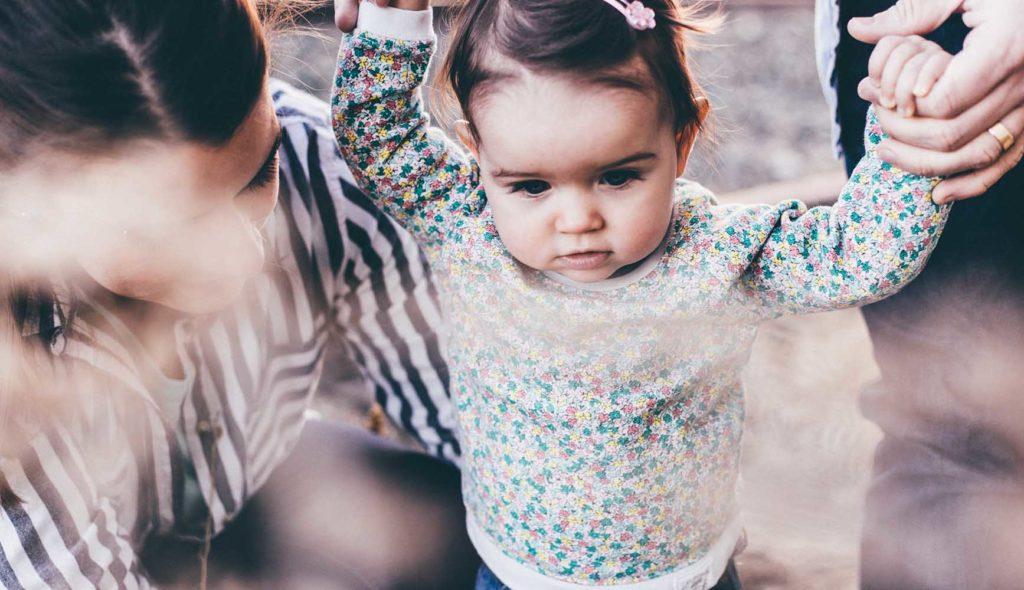よりより歩きの女の子の手を取り歩く3人家族