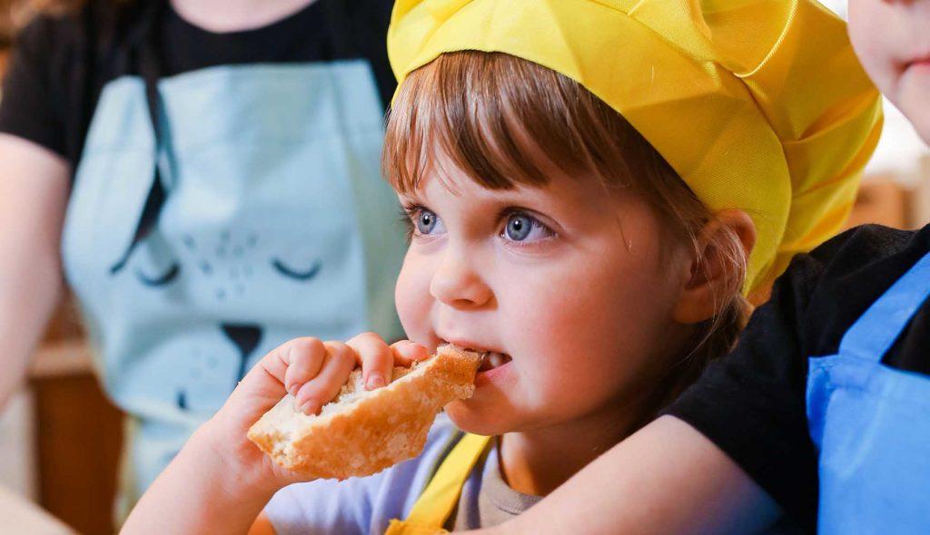 エプロンと頭巾をかぶって、作った料理にかぶりつく子供