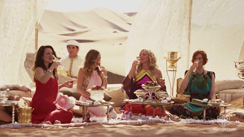 砂漠で美しいコスプレしてシャンパンで乾杯するピクニック中のキャリーと仲間