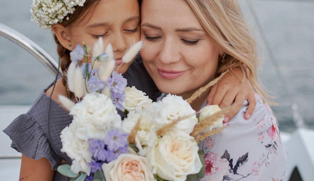 お花の冠をして、花束を女性にプレゼントしてハグする少女