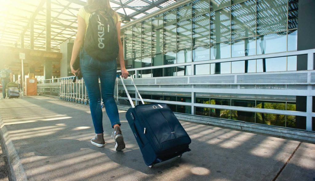 スーツケースをひき空港の道路を歩く人