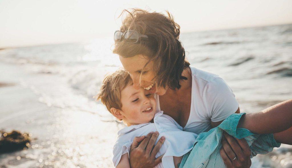 海辺で母親に抱きかかえられ微笑む4歳くらいの少年