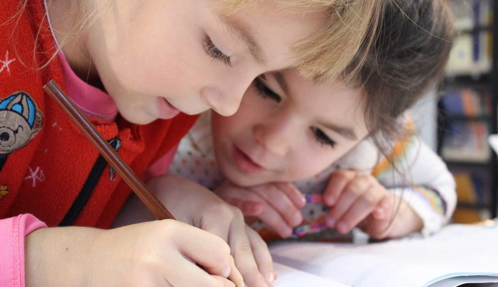 ノートに描く少女を覗き込むもう1人の少女