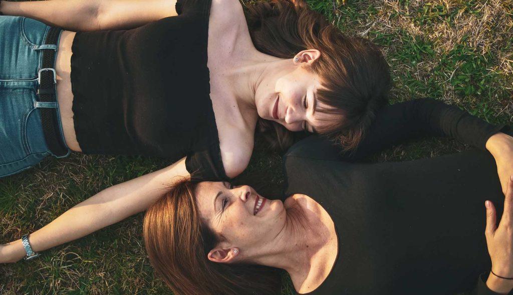 芝生に寝転ぶ18歳くらいに成長した娘と、母親