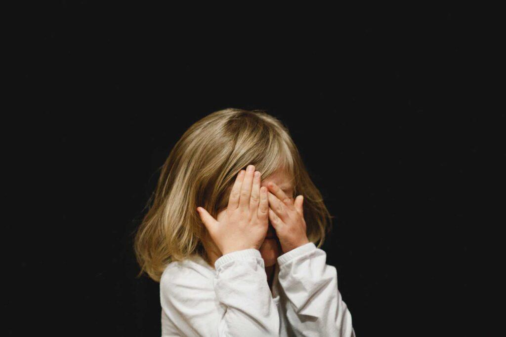まっ黒い部屋で顔を覆ってなく少女