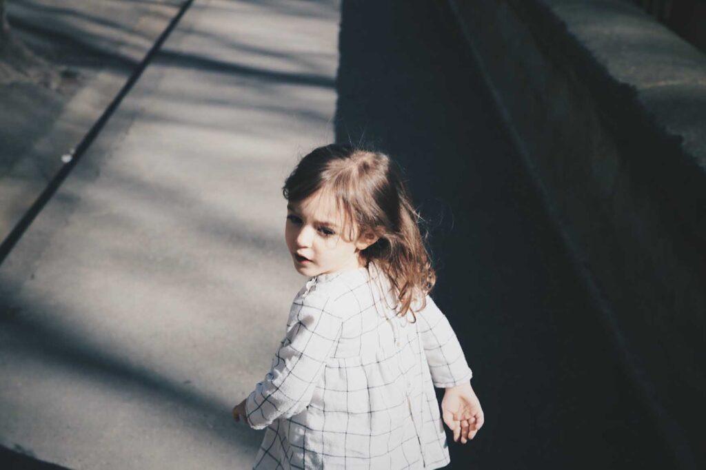 小さな女の子が一人で歩きながら振り返っている