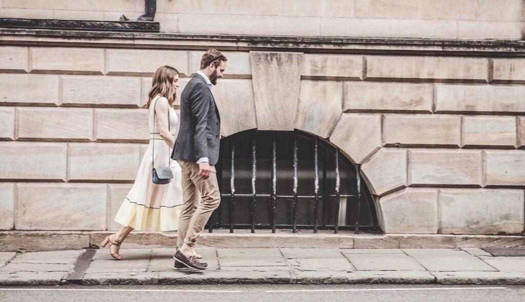 コンクリートの歩道を歩くカップル