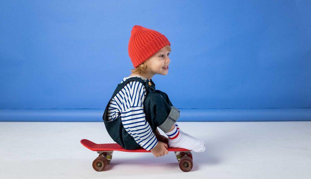 赤いニット帽、ストライプのシャツ、デニムパンツをきた女の子