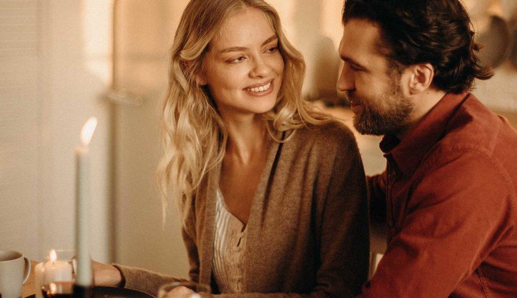 女性の肩に手を置いて見つめあい親密そうに話をするカップル