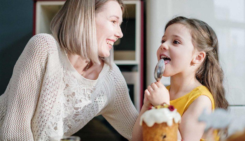 スプーンをペロッと舐める女の子と、微笑んで見つめる女性