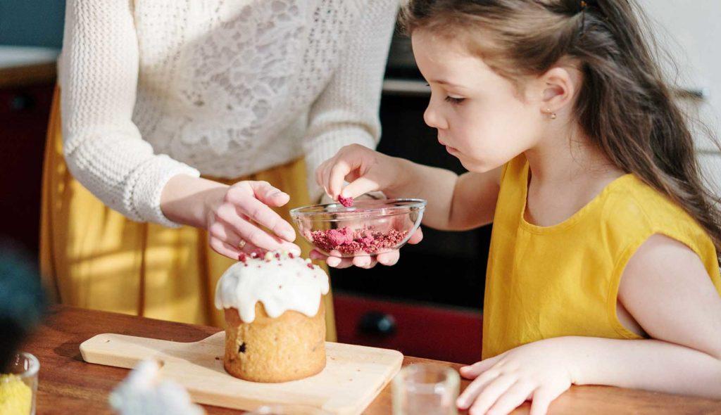 ケーキ作りをする女の子とサポートする女性