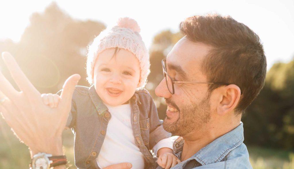 太陽光を背に笑顔の子供を抱っこする男性