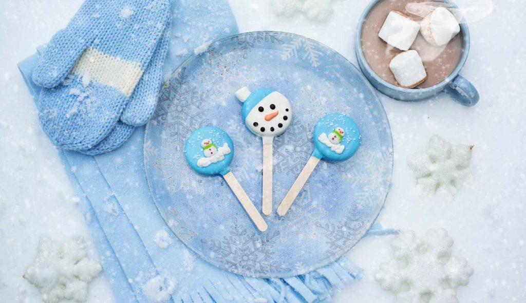 雪だるまのキャラクターの棒付きのお菓子とマシュマロ入りココア、ブルーでコーディネートされたディッシュセットとマフラー手袋