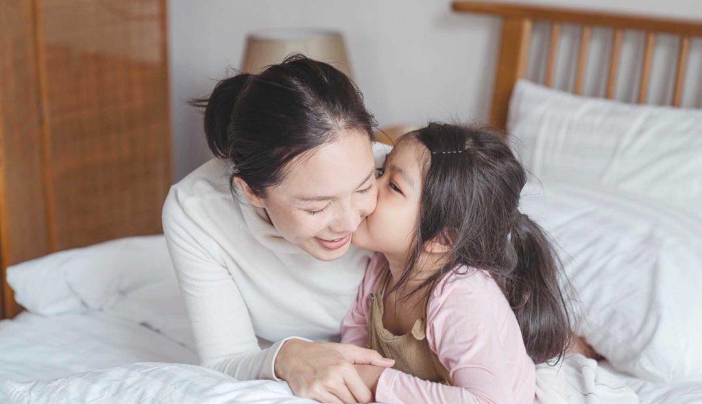 母親の頬にキスする娘