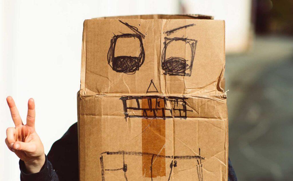 ダンボールに顔を描いてかぶってピースする子供