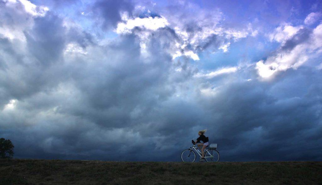 晴れ間も見える曇り空のもと、自転車で大地を駆け抜ける少女