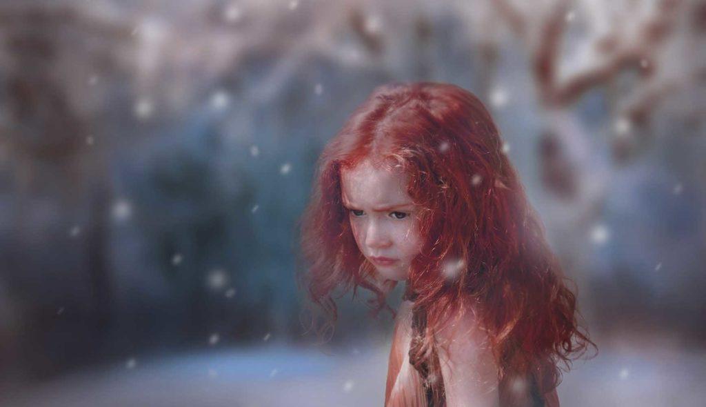 雪の降る舞台、虚ろな表情で演技する赤毛の女の子