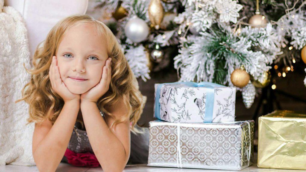 プレゼントの箱の横で頬杖をついて微笑んでる少女