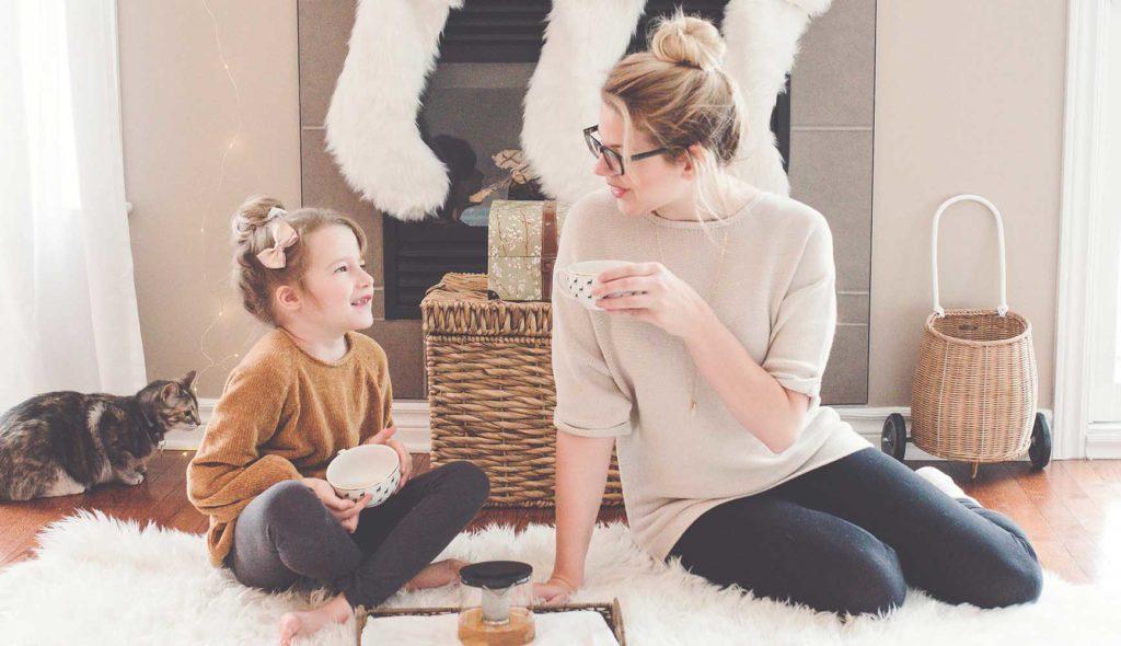 リビングルームでお茶を飲みながら程よい距離感で女子トークする10歳くらいの娘と母