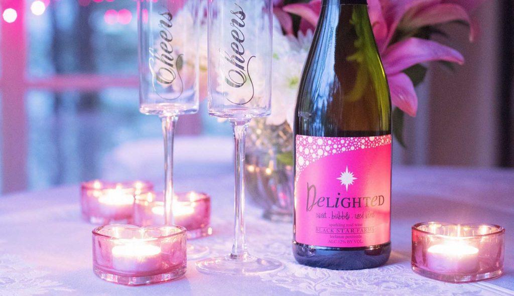 派手なピンク色のラベルのシャンパンとキャンドル、ピンクの花が飾られたテーブル