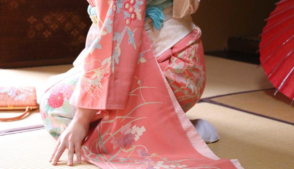 ピンク色の着物を着て和室に座る若い女性