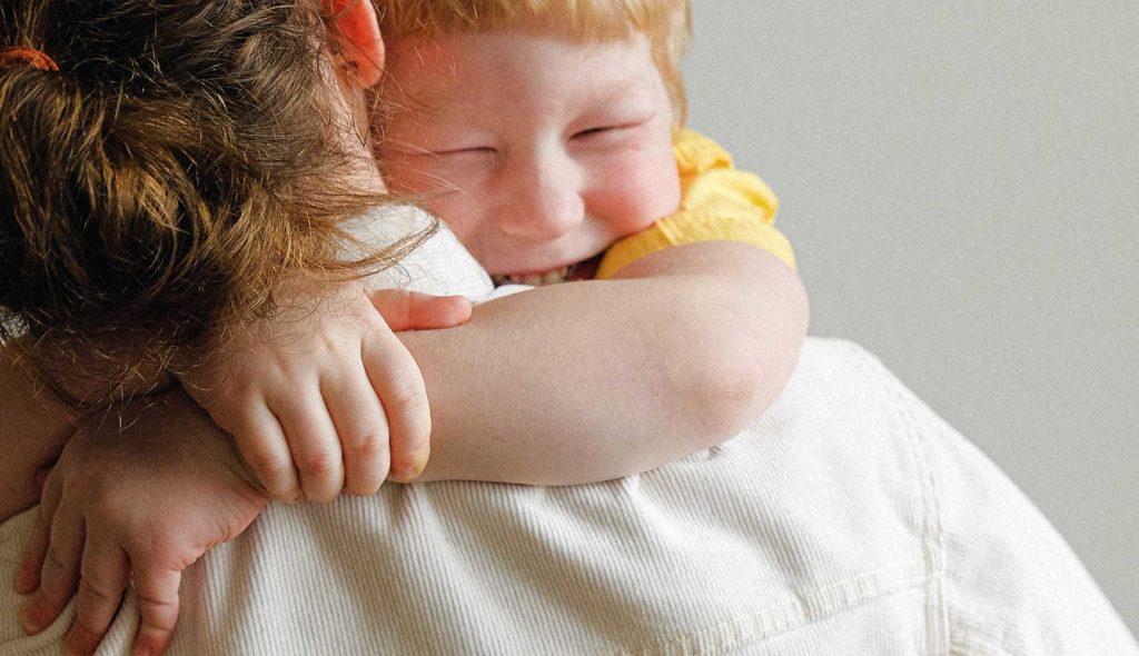 母親に抱きつき満面の笑みの子供