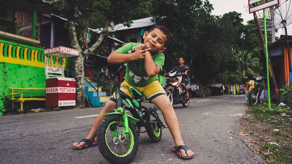 鮮やかな緑の自転車にまたがり笑顔でポーズをとるインドネシアの少年