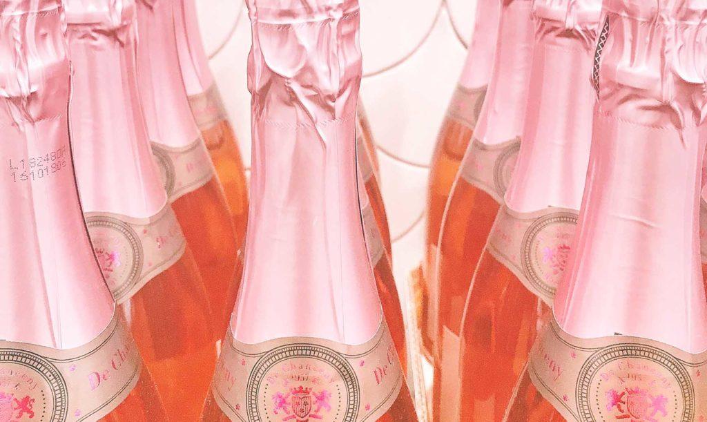 ピンクのシャンパンボトルが並ぶ